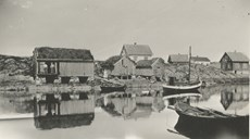 Indreværvågen (bay) in the 1930s, with from left Andersnaustet, Nilsskjåen, and Gullakskjåen. The boat-houses had to be built high above the high tide mark at unsheltered Indrevær. In strong onshore wind and high seas the waves could reach far.