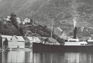 "Dyrdal is the first hamlet on the way into the Nærøyfjord. After a substantial local effort, the hamlet could take its own quay into use on 1 May 1926. The picture shows the old fjord steamer ""Kommandøren"" on her way to make a stop at Dyrdal."