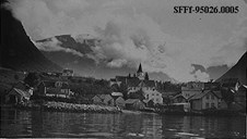 An old picture of Fresvik seen from the fjord. Boathouses and residences are located down by the seaside with the church as a towering backdrop.