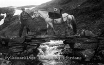 Hans M. Hov and his packhorse on their way across the stone bridge at Vassosen. They are heading for Jordalen by way of crossing the Fresvik glacier.