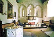 "Vangen church has one of the biggest chancels in the county, and the three windows side by side on the east wall are a characteristic feature of early, Gothic stone churches. The painting to the left is Christen Brun's copy of Rubens' ""Descent from the Cross""."