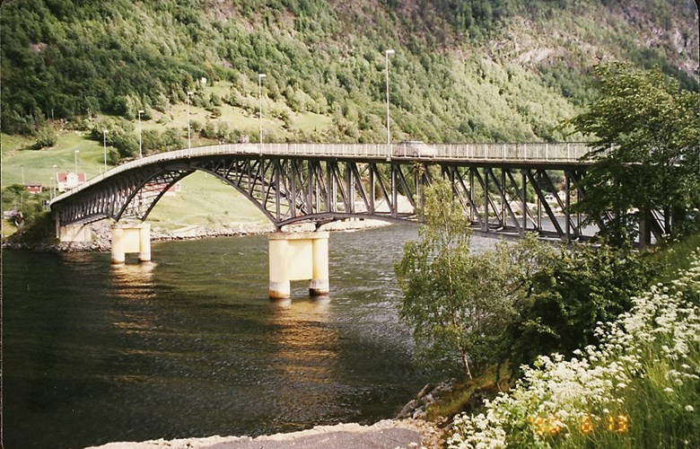 The bridge, opened for traffic in 1958, was designed by the bridge section of the Norwegian Directorate of Public Roads. The bridge is a frame-work steel bridge with an overlying bridge roadway in reinforced concrete. The bridge itself has two side spans with a length of 52 metres, and a main arch span measuring 72 metres in length. In addition there are three minor side spans, one on the Sogndal side and two on the Loftesnes side. The whole bridge is 210.5 metres long. The maximum sailing clearance is 15 metres. The total cost of the project amounted to 2.15 million kroner. The sisters Josefine and Sofie Loftesnes helped raise 30,000 kroner to pay for lighting on the bridge.