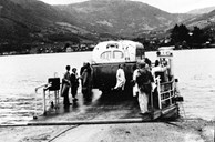 This is the first Loftesnes ferry, photographed after the launching in the summer of 1938. On deck we see some of the workers of 'Løland Motorverkstad' and some others. The chief county road administrator thought it important that as much as possible of the equipment the Public Roads Administration needed was produced in the county. The ferry was built on commission from Torp. The ferry measured 15 metres and with a deck space for four private cars. It was pulled across the strait by a steel wire. The wire was pulled by a crank, driven by a 7.6 hp Sleipner diesel engine.