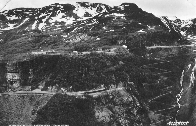 Between Myrdal and Kårdal the railway line makes long curves with many tunnels to avoid areas exposed to avalanches and rockslides. The postcard shows the railway line past the Vatnahalsen station and down the mountainside towards Kårdal. To the extreme right we can see the construction road that was built from 1894-96. This road is today a part of the so-called Navvy Road.