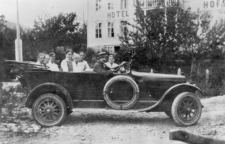 This is the first touring car owned by 'Indre Sogn Automobilselskap AS', a seven-seater Chandler. The car was bought in Bergen in June, 1916, with driver Anton Andersen, who also worked as a car mechanic. He was a so-called 'guarantee driver' at first. Nobody else in Sogndal knew how to drive a car. The passengers are probably Sogndal girls. The speed limit was 30 km/h, and the company had to provide security for any damage before the driving took place even in cases where the damage was not the driver's fault.
