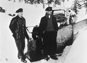 This picture is probably taken after the Second World War. Johan Kjos and Norvald Svedal are working to clear the road of snow. From the Public Road authorities the car company was given a snow-plough, so during the winter of 1936/37 winter routes to Jostedalen could be carried out for the first time. Earlier it had been considered impossible to keep the road open in wintertime.