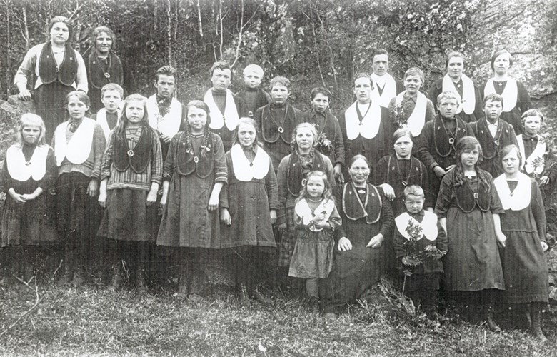 "The children's lodge ""Framhald"" at Bryggja in 1926, wearing their regalia, embroidered pieces of cloth showing rank and position. The adult woman is Anna Myklebust."