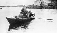 This picture is from 1925. An ordinary rowboat was used to transport passengers. Those going to Bergen had to be transported for half an hour in such a boat in order to get on to the steamship, which at the time stopped at Rognsvåg. Knut Kalgraff is rowing. The adult passengers are Karine Kalgraff, Kristine Kjellbu, and Lovise Kalgraff. The children are Ivar Kalgraff, Marta Kalgraff, and probably Aslaug Turvåg, foster daughter of Karine Kalgraff.