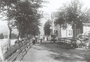 Hafstad Hotell around 1895. A lounge in the front of the picture, and some people in front of the hotel. The river Jølstra can be seen in the direction of Langebrua (bridge).