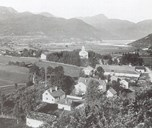 View of Skei around 1895. Nearest are the two farmyards at Indre Skei, the bailiff farm Volden, farm no. 24, and further toward the fjord farm no. 25 at Indre Skei. The old office building is in the yard to the left. At Tåene there are a number of houses reminding of the old Skei: Volden, Indre Skei, and the captain farm near the church. The old vicar residence is outside the picture to the left.