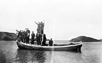 "A typical shore seine vessel, the 30-foot ""Gåsværgavlen"" with a 12 HP Rapp engine, leaving Gåsvær. In 1936, they caught 12,000 hectolitres with this boat alone near Gåsvær. The picture shows a happy crew being transported home after the winter fisheries."
