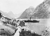 Mundal in Fjærland on a summer's day about 1900. This was the centre of Fjærland with a hotel, shops, post office, and shipping agent. We see the steamer backing off from the quay.