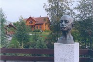Bust of the founder, Gert Falch Heiberg (1871-1944). In the background 'Helgheimstova' - the first school building of 'Sogndal folkehøgskule' dating from 1874.
