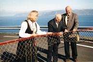 "The people of Kråkenes had made their own ""ribbon"" for the opening of the road, and one of the ingredients was an old salmon net. Even if salmon fishing no longer is an important industry at Kråkenes, the salmon net and the road symbolize new times and new challenges. At the ribbon cutting ceremony: Mayor Liv Henjum, chairman of the county council Sjur Hopperstad and chief road administrator for the county Lars Lefdal."