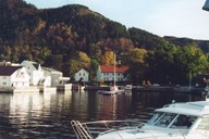 The Selje vicarage has a fine location in the innermost part of the bay of Seljevågen. The house called 'Skulen' (the school) is the white building to the left of the main building. To the far left in the picture is the house called <i>Frimannsbuda,</i> , today owned by Selje Hotell, but was previously owned by the vicar.