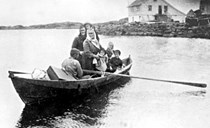 "Passengers from Kolgrov on their way to the steamship, which at the time had to be boarded in the bay of Rognsvågen. An ordinary Nordfjord rowboat was used, and it took them around half-an-hour to get to SS ""Gula"". Knut Kalgraff is rendering people and luggage service."
