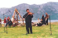 "Church service at Kyrkjeneset, Losna, in connection with the Losna festival in 1999. Vidar Underseth is playing the ""harding"" fiddle. Under the twisted logs the church bell hangs."