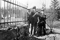 In 1935, Marie Landmark was buried at Fredensborg. From left to right, Jens Tyssedal, Mons Bakkebø and Knut Bakkebø stand singing at the gate of the private graveyard.