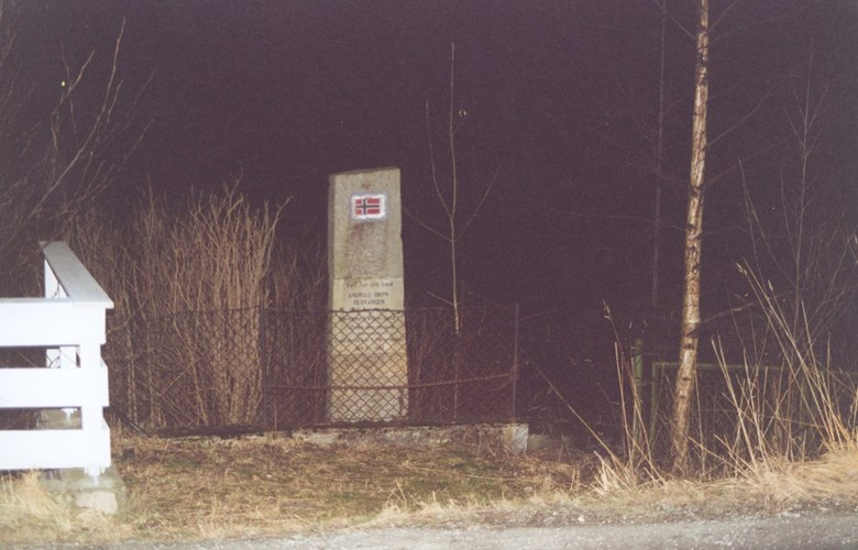 The memorial stone for Andrias Bryn is located on the eastern side of the road at the village of Gudvangen. It is surrounded by lattice fencing.