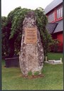 The Schreuder memorial at Stedje church in Sogndal. The stone has a height of some two metres (about seven feet)and the rock is 'Hafslo granite'. The stone was found in this shape at Ølnes. On the bronze plaque is inscribed: 'Hans Paludan Smith Schreuder (* = born) KJØRNES, SOGNDAL 18 June, 1817  (V = died) 27 January, 1882 South Africa.  The first missionary in the Norwegian Missionary Society - 'God's will - the world's salvation' - Cf.1 Timothy 2,4. Erected 1992.'  (1. Tim. 2,4: .. who will have all men to be saved and to come unto the knowledge of the truth.)  (1. Tim. 2,4 står: .. han som vil at alle menneske skal verta frelste og koma til å kjenna sanningi.)