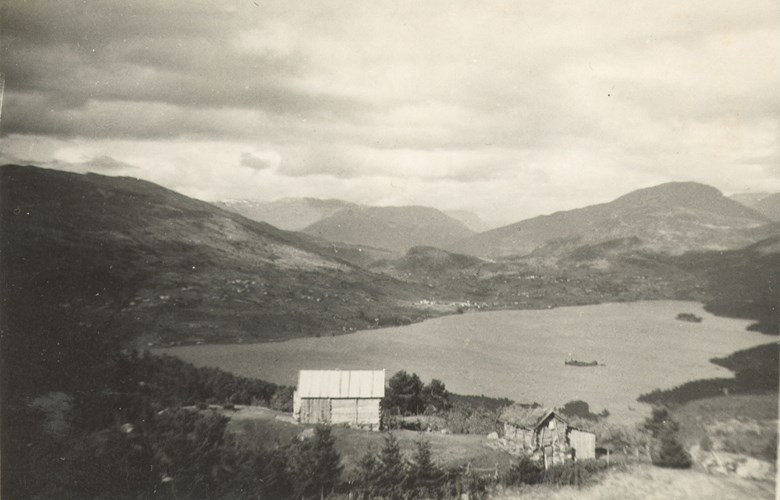 The Steigastølen mountain farm with the lake of Hafslovatnet and the village of Hafslo in the background. 'Nyaselet' (the new building), built in 1940, to the left, and the considerably smaller old building - 'Gamlaselet'. To the right in the picture we can see a part of the cultivated field,  (norwegian: slåttegjerdet). This field is called 'Strandagjerdet'.
